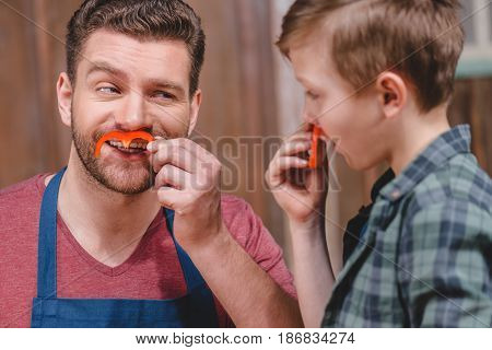 Smiling Father And Son Having Fun With Pepper Moustaches, Dad And Son Cooking Concept