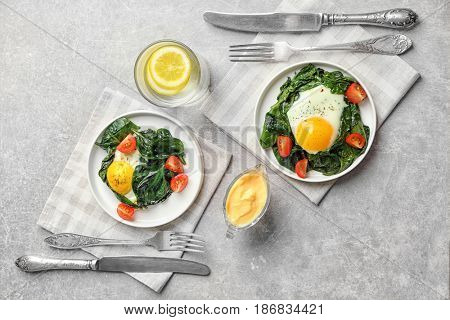 Delicious eggs Florentine with tomatoes on kitchen table poster