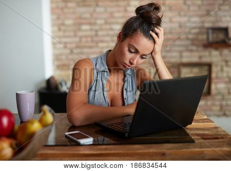 Sad woman sitting at desk, using laptop, looking down.
