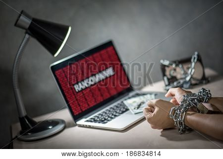 Hard disk file locked with monitor show ransomware cyber attack internet security breaches on laptop computer user hand tied up by chains and lock concept