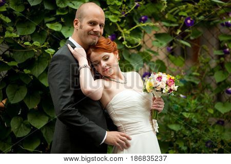 Stunning Woman With Red Hair Leans To A Bald-headed Man