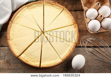 Tasty homemade cheesecake, eggs and whisk on wooden table