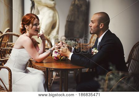 Bride Tells Something To A Bald-headed Groom Sitting At The Cafe Table
