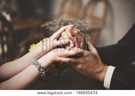 A closeup of newlyweds hands held tightly together