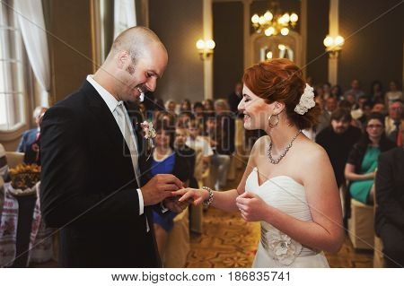 Happy Bald-headed Groom Puts A Wedding Ring On Tender Bride's Finger