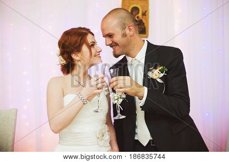 Groom And Bride Cland Glasses Standing In The Restaurant Hall