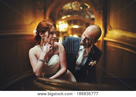 Bald-headed Groom Looks At A Bride Standing Behind A Her In A Wooden Hall