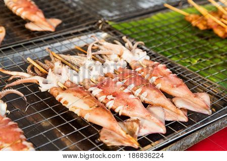 cooking, asian kitchen and food sale concept - squids on grill at street market