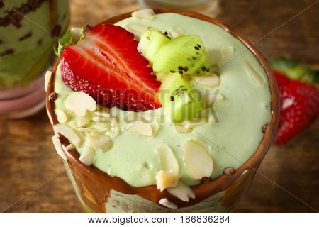 Delicious parfait with fruits on wooden background