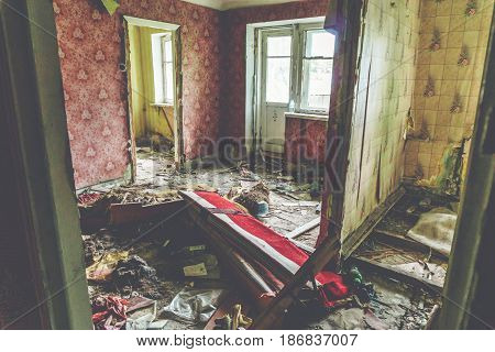 Room in abandoned house, broken furniture on the floor, habitation of homeless people