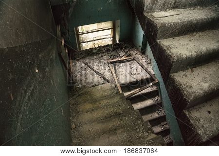 Staircase in an abandoned ruined house or building, broken glass on the floor, broken windows