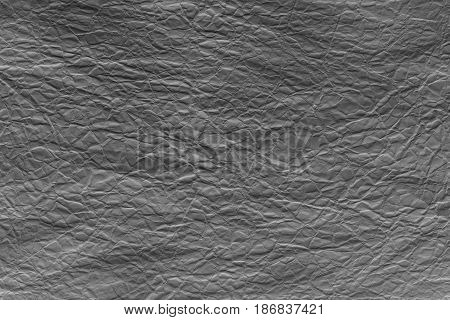 Black crumpled sheet of paper. Grungy background texture with copy space for text or image.