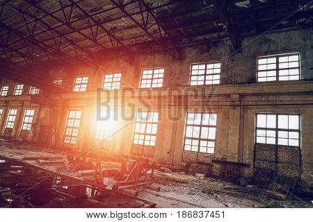 Large empty abandoned warehouse building or factory workshop, sunset effect