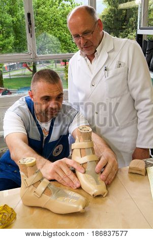 Doctor And Worker Preparing Orthopedic Insoles For A Patient