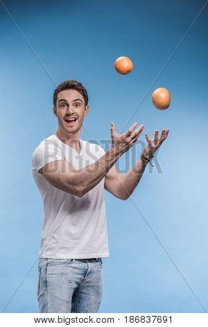 Smiling Young Man Juggling With Fruits Isolated On Blue
