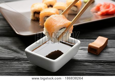 Dipping tasty roll into bowl with soy sauce on wooden table, closeup