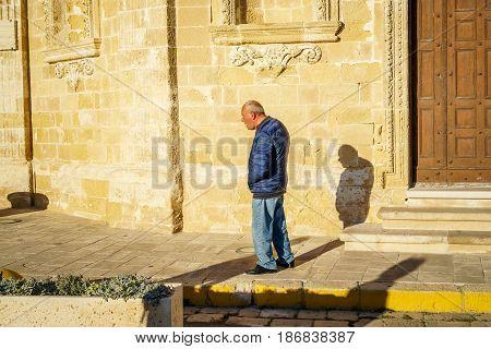 Gallipoli Italy - March 3 2017: Elderly man walking through sunny street of Italy