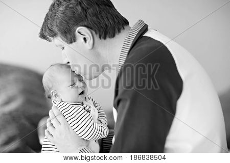 Happy proud young father having fun with newborn baby daughter family portrait togehter. Dad with baby girl love. New born child looking on dad. Bonding family new life. In black white