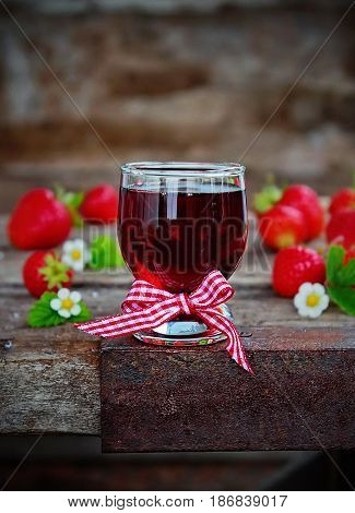homemade strawberry liqueur, fresh strawberries and flowers on wooden background