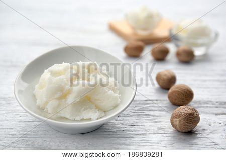 Shea butter in bowl on wooden background