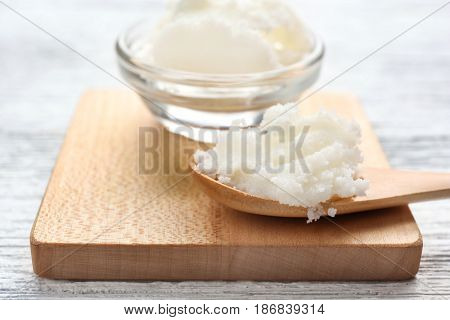 Shea butter in bowl and spoon on wooden board, close up