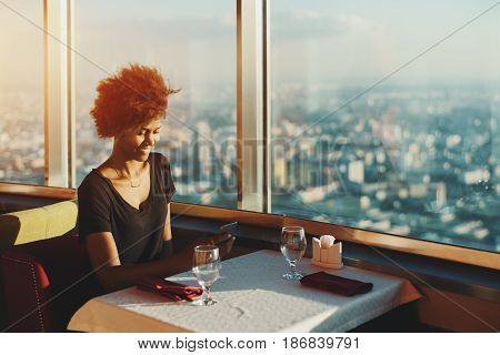 Charming black teenage girl with curly afro hair sitting in modern restaurant on the top of very high skyscraper near window with cityscape view having online chat with her sister using smart phone