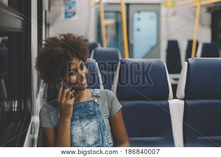 Cheerful young black lady talking with her sister via smartphone while sitting in coach of electric train mixed cute smiling teenage female calling her boyfriend via cell phone while going by train