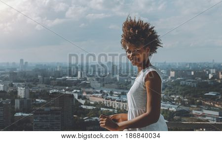 Charming black girl with curly african hair is standing on very high balcony of skyscraper on observation point and looking in camera with copy space area for text message or logo sunny summer day