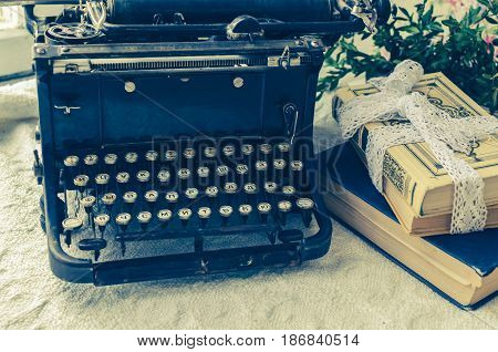 Vintage typewriter and books on the table writer area. Retro style image.