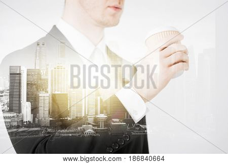 people and business concept - close up of businessman drinking from take away coffee cup over city with double exposure