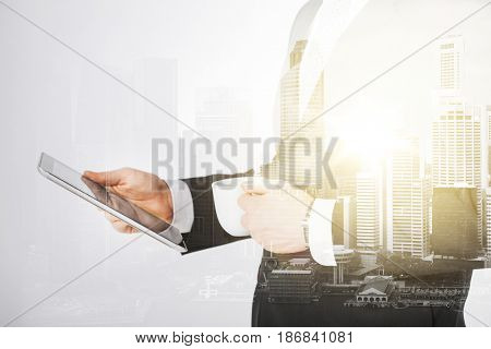 people, business and technology concept - close up of businessman with tablet pc computer and cup of coffee over city with double exposure