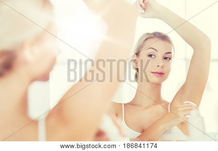 beauty, hygiene, morning and people concept - young woman applying antiperspirant or stick deodorant and looking to mirror at home bathroom