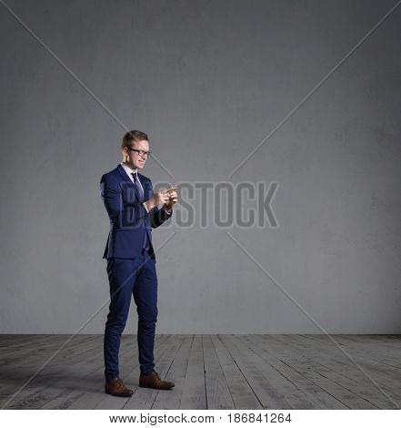 Businessman with smartphone standing in front of a grey wall. Business, office, concept.