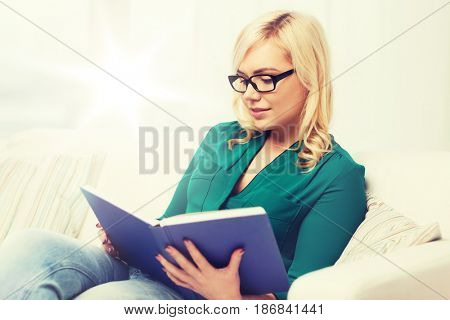 leisure, literature, education and people concept - young woman in glasses reading book at home
