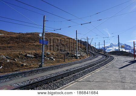 Beautiful scenic train railway transportation on alp with snow mountain in daylight Switzerland.