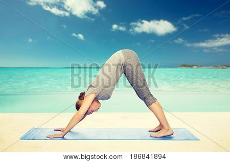 fitness, sport, people and healthy lifestyle concept - woman making yoga in downward facing dog pose on mat over beach background