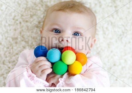 Cute adorable newborn baby playing with colorful wooden rattle toy ball