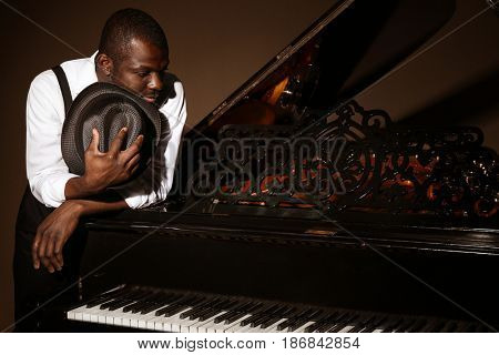 Afro American man holding hat beside piano