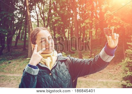 Pretty young woman blogger takes selfie portrait at action camera and shows peace sing by fingers. Blogging, vlog, videoblog and popular mass media concept