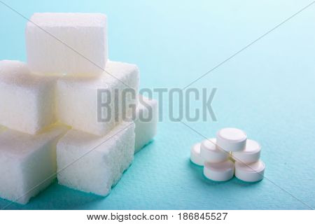 Sugar substitute. Cubes sugar and stevia pills on a green background