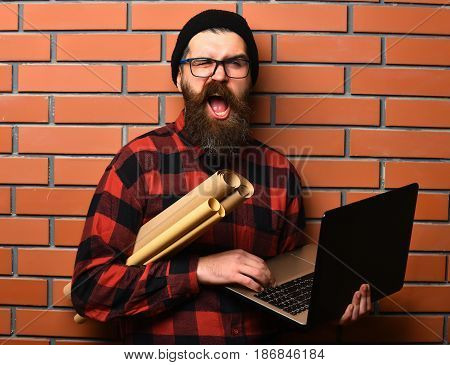 Bearded man long beard. Brutal caucasian unshaven hipster holding laptop and craft paper rolls in red black checkered shirt with hat and glasses on brown brick wall studio background