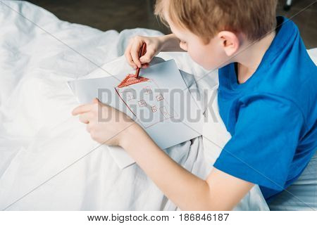 Side View Of Little Boy Drawing Picture While Lying In Hospital Bed
