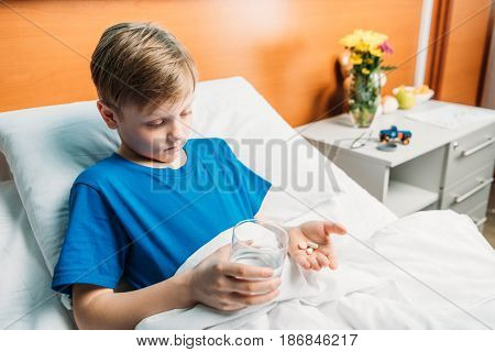Portrait Of Upset Boy Holding Glass Of Water And Medicines In Hospital Bed, Hospital Patient Care Co