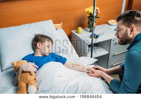 Side View Of Pensive Dad Sitting Near Sick Son With Drop Counter In Hospital Bed