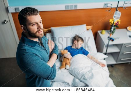 High Angle View Of Pensive Dad Standing Near Sick Son In Hospital Bed