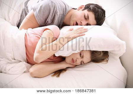 Young irritated woman lying in bed with snoring husband at home