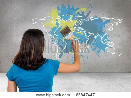 Digital composite of Woman painting a Colorful Map with paint splattered wall background