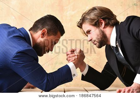 Business partners crisis and confrontation concept businessmen arm wrestling in office