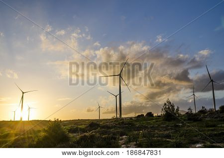 Wind turbines during a dramatic sunset lens flare on the lower left adds further drama to the shot