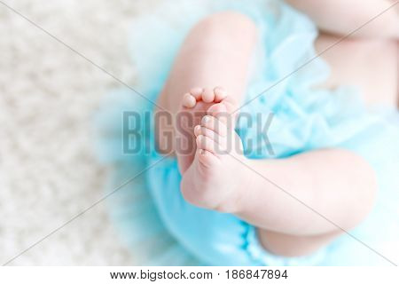 Close-up of legs and feet of baby girl on white background wearing turquoise tutu skirt. Cute little child laughing and smiling. Happy carefree baby. Childhood, new life concept.